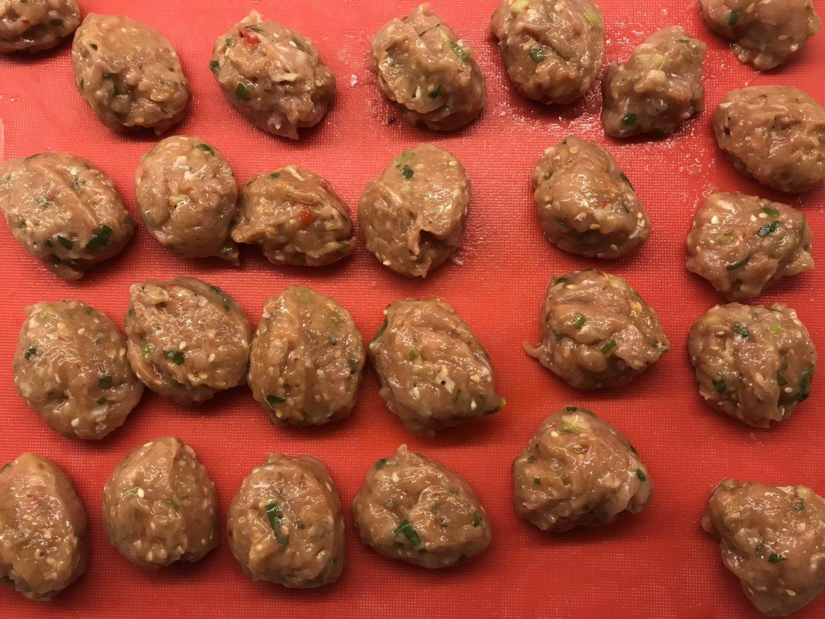 Ferdigrullede kyllingkjøttboller på vei i stekepannen
